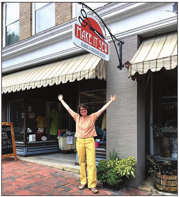 MAKE IT SEW owner Accacia Mullen celebrates the new sign for her store. In 2019, Main Street Lexington offered over $2,000 to enable store owners to purchase new signs and awnings.