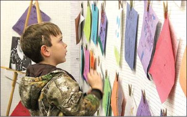 AN ENDERLY HEIGHTS Elementary student checks out the published stories displayed at the Enderly Author's Gallery. The Author's Gallery featured stories from students in the Writer's Workshop format at Enderly. (Harrison Mines photo)