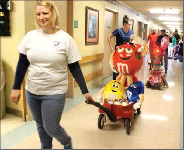 Wittnie Mason, speech language pathologist, pulls the M&M float in the parade. Aegis Therapies' staff partnered with Shenandoah Valley Health and Rehab staff to prepare floats of various themes and sizes.