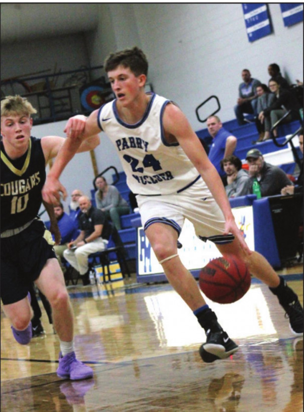 FIGHTING BLUE junior guard Will Dunlap drives toward the basket as Covington's Samuel Akers defends him. Dunlap led all players with 22 points and grabbed 10 rebounds. (Ronnie Coffey photo)