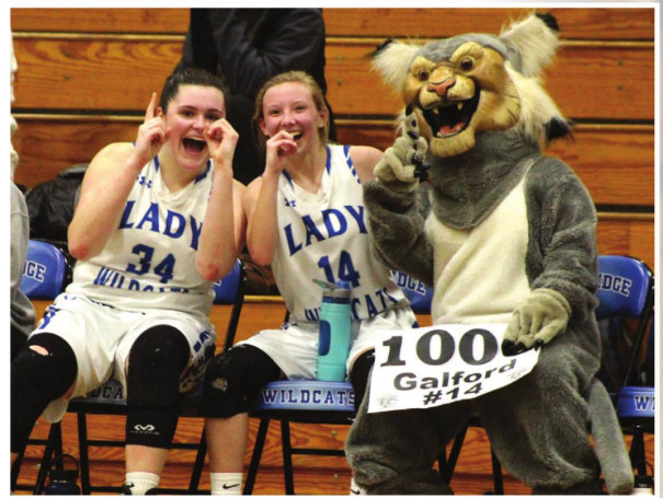 ABOVE, RC senior guard Emily Galford (14) celebrates on the bench with teammate Graceon Armstrong and the Wildcats' mascot after scoring her 1,000th career point. AT RIGHT, Galford's father, Wesley, lifts her up to be honored by fans after she made the free throw to reach the milestone. Also joining Galford on the court is her mother, Kim. (Stephanie Mikels Blevins photos)