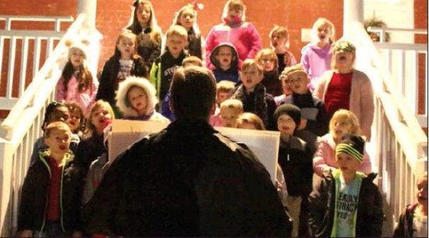 Enderly Heights Elementary School children sing holiday songs outside the Paxton House. (Stephanie Mikels Blevins photo)