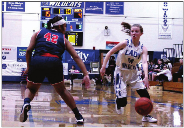 RC SENIOR guard Emily Galford takes the ball down the court while Liberty's Machenze Flood backs up on defense during the Wildcats' 53-26 win. Galford scored 14 points. (Stephanie Mikels Blevins photo)