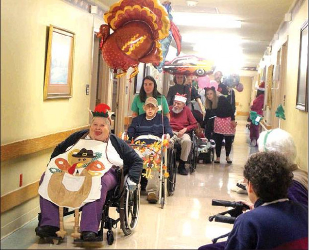 AT IMMEDIATE RIGHT, among the youngest participants in the first Thanksgiving Parade at Shenandoah Valley Health and Rehab was 1-year-old Felicity Gessell, with her mother Alicia Gessell. AT FAR RIGHT, residents and staff enjoy the parade. (all photos by Stephanie Mikels Blevins)