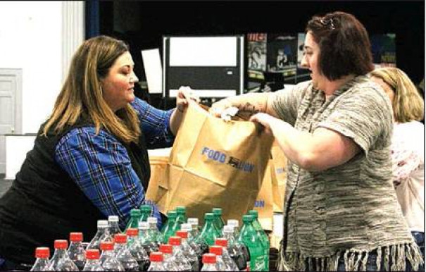 PARRY McCLUER Middle School teacher Courtney Dickinson-Austin helps distribute a Thanksgiving meal prep bag to a parent of a PMMS student. Parents of each student were invited to pick up a free Thanksgiving turkey meal last Friday as part of a school community outreach initiative by faculty and staff. (Harrison Mines photo)