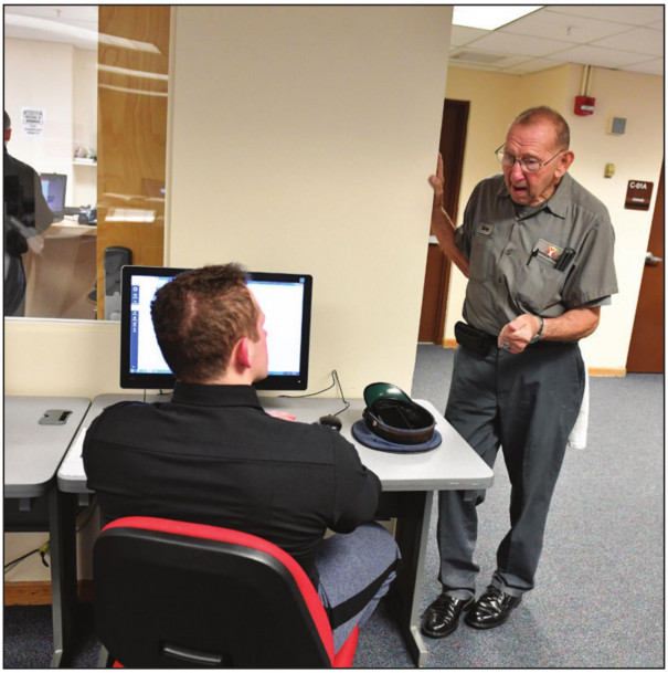 BARRACKS custodian Barney Odend'hal chats with cadet Cody Luper while cleaning up the barracks study room. (VMI photo by Kelly Nye)