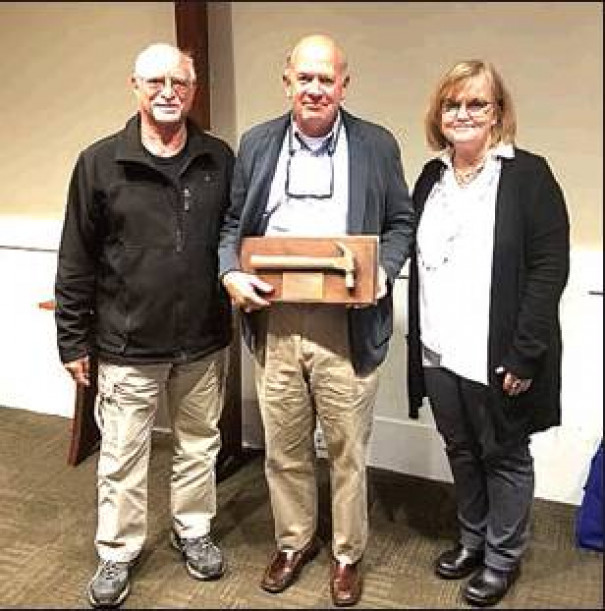 STEVE NEAS is presented with the Golden Hammer Award by Stan Ponce, chair of the Rockbridge Area Habitat for Humanity board; and Lynne Johnson, executive director.