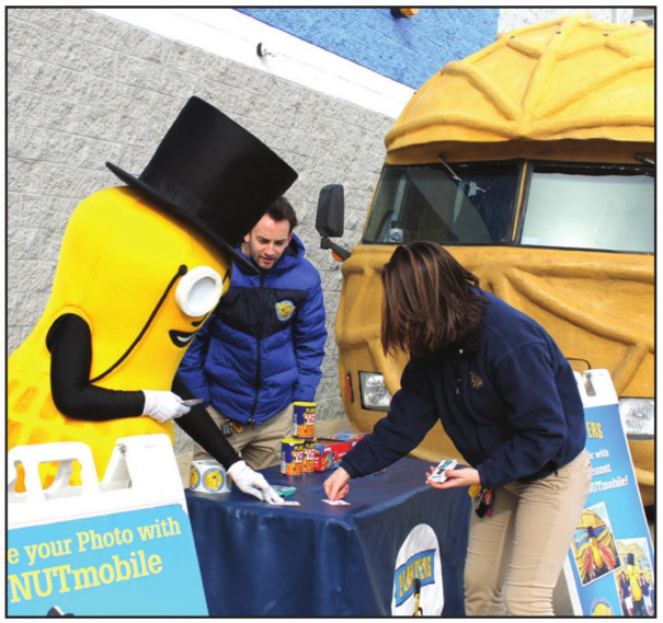 """The Planters NUTmobile – a 26-foot-long peanut on wheels - made a stop at the local Walmart Friday afternoon, with Mr. Planter Peanutter meeting with area residents and handing out snacks. ABOVE, a resident plays a game of """"War"""" with Mr. Peanutter to try to win additional snacks. AT LEFT, Kaden Dorey gets his photo made with the celebrity guest. (Stephanie Mikels Blevins photos)"""