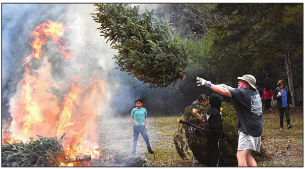 Another Christmas tree is tossed onto the fire at Lime Kiln's annual tree burn last Saturday. Area residents were asked to bring their trees along with assorted greens from the Christmas holiday for the burning. Trees collected from the curbsides in Lexington were also contributed to the bonfire. Rain threatened throughout the day, but only a few sprinkles fell during the afternoon. (Joann Ware photo)