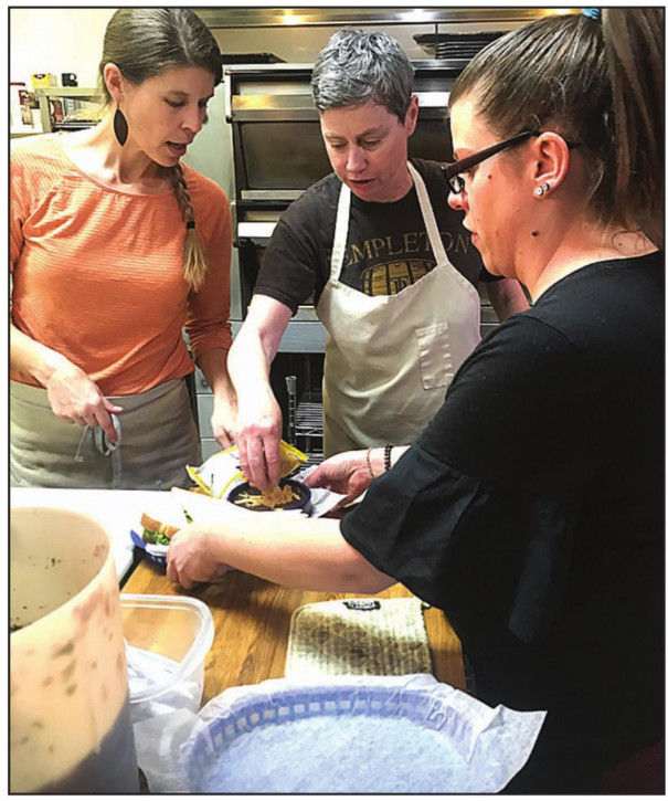 BLUE SKY'S new owner, Beverly Drake (center), prepares a sandwich during a busy lunch hour with employees Stephanie Scott (right) and Lynn Alexander. Blue Sky reopened under Drake's ownership just last week. (Katie Doar photo)