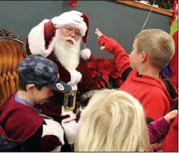 Santa gives a fist bump to a child during his visit to White's Travel Center Saturday afternoon.