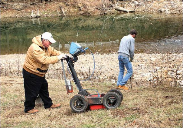 MATTHEW TURNER (left) of GeoModel in Leesburg assists Dan Altman (right) in the search for buried treasure at Jordans Point Park by scanning the ground with radar. Altman traveled to Lexington to search for treasure that he believed to be buried in the city. (Harrison Mines photo)
