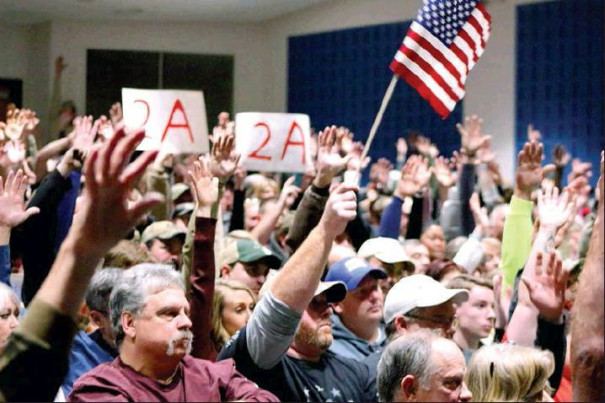 ROCKBRIDGE COUNTY residents raise their hands, along with a few signs and an American flag, when asked if they support the Second Amendment sanctuary resolution before the Board of Supervisors Monday night at the Rockbridge County High School auditorium. (Stephanie Mikels Blevins photo)