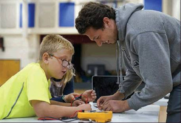 ALEX SENDER, a sophomore at W&L, teaches a child about electrical circuits at an after-school program developed in partnership with the Rockbridge Area YMCA. (W&L photo)
