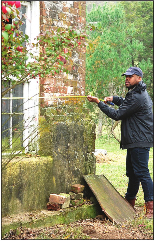 JUSTIN REID with Virginia Humanities takes measurements at the slave dwelling at White Hall in the Brownsburg area last fall. He will be among the state officials speaking at the Feb. 22 forum.