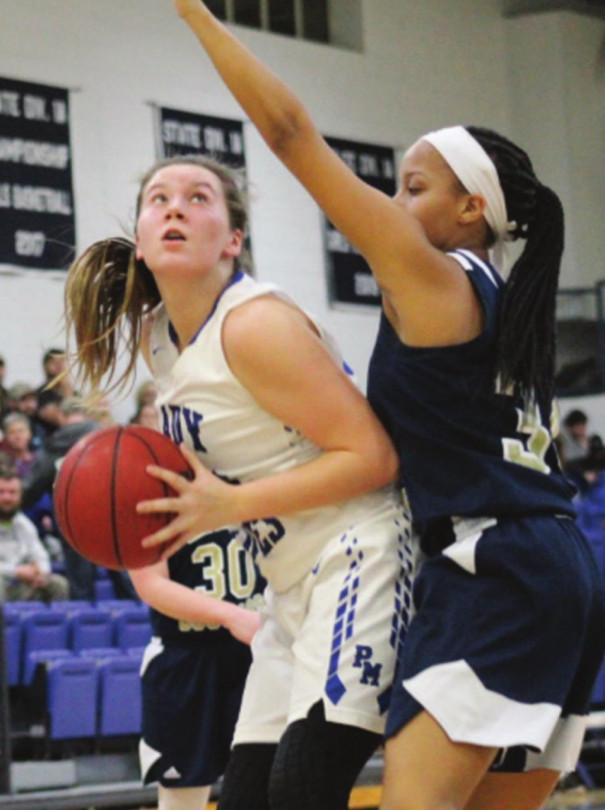 PM SOPHOMORE forward Grayce Henson looks to the basket as Covington's Amiah Hunter guards her. Henson led the Blues with 12 points. (Ronnie Coffey photo)