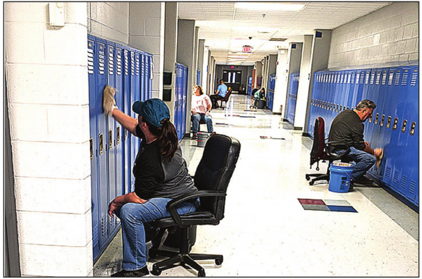 STAFF at Parry McCluer High School scrub down lockers last Thursday morning. Buena Vista schools were closed Thursday and Friday because of an outbreak of flu and other illnesses. Employees reported to work to scrub down and otherwise disinfect the school facilities and buses.