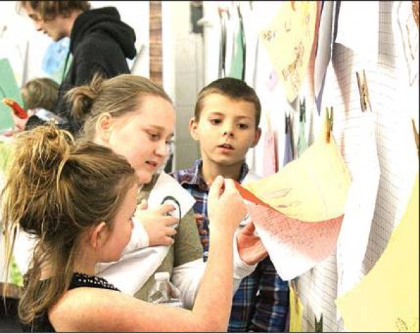 STUDENTS read the narrative works of their classmates at the Enderly Author's Gallery in the Wilford P. Ramsey Center last month. Some students had the opportunity to bring their stories to life through short films. (Harrison Mines photo)