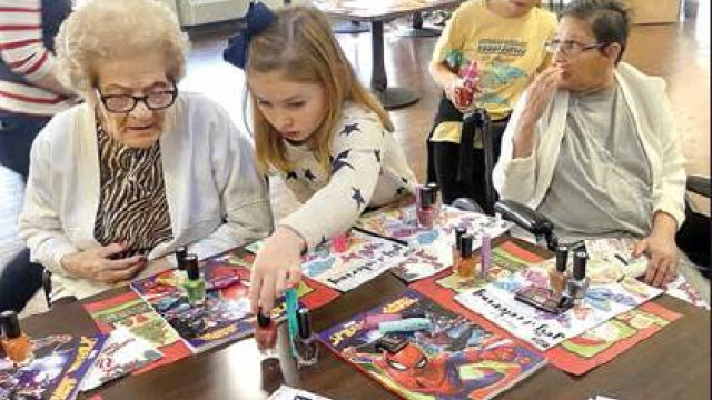 Members of Central Elementary School's Destination Imagination team visited Heritage Hall last week, bringing with them items they had purchased for the residents – and the gift of time. Here, Central Elementary student Addie Brown shows one of the Heritage Hall residents some nail products as well as coloring books to choose from, while Central student Maddie David (in back) looks on with another resident. For a story on the team's visit, see page 5. (Claudia Schwab photo)